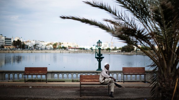 An elderly Libyan man sits on a bench next to an artificial lake between the waterfront and Tripoli's iconic Martyrs' Square, formerly Green Square, on October 5, 2011.  AFP PHOTO/MARCO LONGARI        (Photo credit should read MARCO LONGARI/AFP/Getty Images)